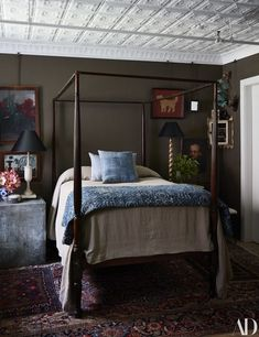 The bedroom features a 19thcentury canopy bed with a linen cover by Charvet Editions. On walls Farrow  Ball's mouse's back. handsome bedroom #johnderian
