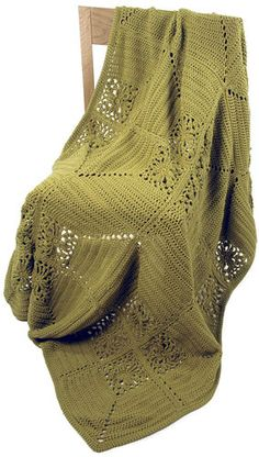 Andalusia is a solid colored crocheted throw with a modern arrangement of double crochet and floral motif blocks.