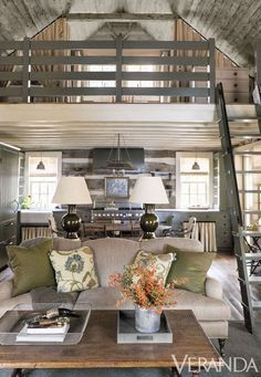 The cabin's traditional furnishings and cozy fabrics add up to understated style.   Custom sofa in a Rogers & Goffigon fabric; crewel pillows, Old World Weavers; olive pillows in alpaca, Sandra Jordan; coffee table, Dos Gallos; lamps, Christopher Spitzmiller; railing and ladder in Dakota Woods Green, Benjamin Moore.      - Veranda.com