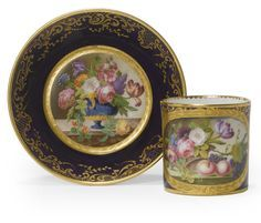 A SEVRES BLEU NOUVEAU-GROUND CUP AND SAUCER 1772 (gobelet litron et soucoupe) each piece painted with a basket of flowers or fruit within a tooled gilt-edged panel reserved on a deep blue ground within an elaborate gilt scrollwork border,