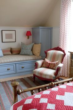 another mix of patterns, textures & colors from Sarah Richardson's country house - stock cabinets create the seating and storage under the eaves with padded cushion and pillows, victorian chair made modern with striped fabric, striped rug like Dash & Albert, brass bed with red and white quilt, sconce lighting with red shade -