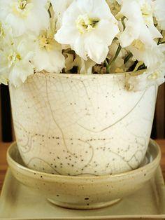 Arranjo de flores brancas em vaso branco de ceramica