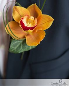 Lovely burnt orange cymbidium orchid boutonniere with looped grass accent detail. http://floristiqart.com/en