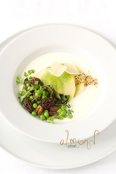 Sunchoke ravioli with quail egg yolk on fresh goat cheese sauce with morel-pea-dandelion ragout and roasted hemp seeds