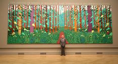 British artist David Hockney poses in front of his painting entitled The Arrival of Spring in Woldgate, East Yorkshire in 2011 (twenty-eleven) at the opening of his exhibition David Hockney RA: A Bigger Picture in the Royal Academy of Arts on January 16, 2012 in London, England. The exhibition is the first major showcase of David Hockney?s landscape work to be held in the UK.