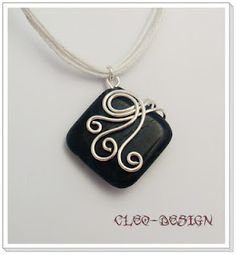 Wire wrap on black glass or polymer pendant. Love the swirl.