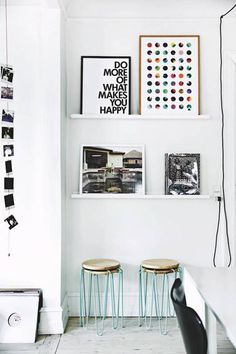 Minimalist living space with floating shelves styled with colorful art, and neon stools below