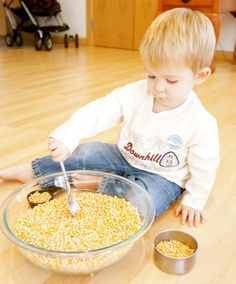 Scooping popcorn (or rice). My son does this in his Montessori school. It's supposed to help him learn to use utensils. Need to remember this one, but need to watch him carefully so it doesn't go in his mouth!