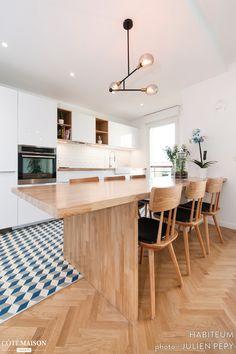 Une grande table en bois à l'esprit bar trône au milieu de la cuisine