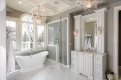 Simple, traditional bathroom in all white with free-standing tub, glass door shower, white vanity and marble floors | Riordan Signature Homes Inc.