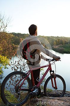 Man with a bicycle stands near the river by Olhaafanasieva, via Dreamstime