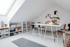 Pomieszczenie zlokalizowane na poddaszu stało się funkcjonalnym biurem domowym, dzięki właściwemu zagospodarowaniu przestrzeni. Miejsce pod oknem zabudowano wykonanym pod wymiar niskim regałem – w sam raz na książki i ozdobne drobiazgi. Duży blat wsparty na koziołkach służy za biurko, przy którym pracować mogą aż cztery osoby.