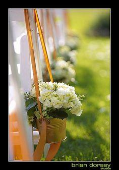 buckets of flowers on garden hooks for outside ceremony. i love this idear cause ite soo in inexpensive!!!!!!!