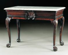 AN IRISH GEORGE II MAHOGANY SIDE TABLE Circa 1750, originally with a wooden top The later rectangular grey-veined white marble top, over a frieze with Greek-key centered by a shell, on cabriole legs and ball-and-claw feet, headed by a fanned shell 32in. (81.5cm.) high, 44½in. (113cm.) wide, 26in. (66cm.) deep