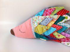 """כרית מעוצבת לחדר הילדים בצורת קיפוד.  הכרית מרופדת, ותפורה בעבודת יד בתפירה מקורית.  הכרית עשויה מכותנה, ה""""קוצים"""" של הקיפוד בנויים מטלאים משולשים ממגוון בדים צבעוניים ומעוצבים.  עין הקיפוד רקומה בחוט ומחט, והאף מצויר בצבע חום כביס.  צדו האחורי של הקיפוד תפור מבד כותנה כחול עם נקודות.  ניתן לכביסה. עם הקיפוד מקבלים הוראות כביסה.  אורך- 39 ס""""מ, גובה- 20 ס""""מ"""