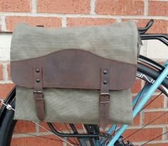 This simple canvas and leather pannier is great for everyday use. It measures 12.5x11x3.5 and has one main compartment that has two small side