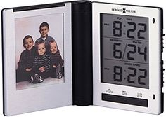"""A slim folding travel alarm clock with a photo holder. Black and brushed silver finish. The LCD displays the month, day, and time in a 12- or 24-hour format. Dual time format, snooze alarm, and display light at a touch. Quartz, alarm movement includes the battery. Size: H 3"""" W 2.75"""" D .75"""""""