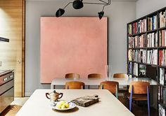 Kitchen/dining space with large art, a wall of books, and a dining table