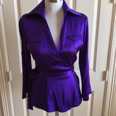 DVF Purple Silk Top Beautiful DVF top has the following features:  purple silk material, wrap around waist style, 4 pockets (2 at top and 2 side slits) includes button sleeves to roll up if desired, 23 inches from shoulder to hem, 95% silk/5% spandex, Size 8.  In excellent condition!  Got soooo many compliments in this top.  It accentuates the bust area! Wear with jeans, skirts, or pants! This is a very nice top!  Diane von Furstenberg Tops