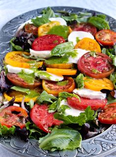 Insalata Caprese with Basil Vinaigrette. The perfect summertime dish. August heirloom tomatoes and fresh mozzarella, drizzled with fresh basil dressing.
