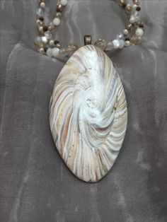 By Debby Wakley Faux shell, semi translucent polymer clay toned with alcohol inks and pastels. A simple pendant on a colour coordinated beaded necklace