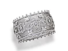 A diamond bangle bracelet the hinged openwork bangle of lace motif, accentuated at the top with marquise and round brilliant-cut diamonds; estimated total diamond weight: 10.00 carats; mounted in oxidized eighteen karat white gold