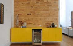 O bufê amarelo com desenho da arquiteta Luita Trench ganha destaque na frente da parede feita com caixas de vinho