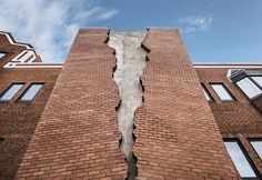 alex chinneck fractures the façade of a brick building in london