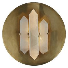 The Halcyon Round Wall Sconce by Visual Comfort brings a unique decorative presence to your living space, featuring a trio of faceted quartz crystals that suspend from a round Antique-Burnished Brass wallplate. The crystals act as shade for a pair of light sources, concealing and refracting their illumination for a soft ambient effect.