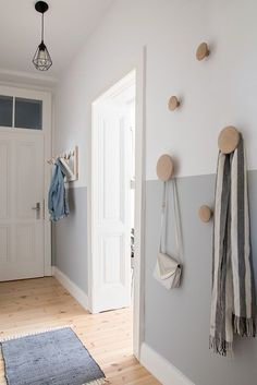 Beautiful modern and Scandinavian inspired entryway with a half-painted wall and some wooden coat hooks.