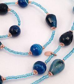 Gocce e perle di agata blu e vetro di Murano montate con in argento 925 placcato rosa.  Può essere portata doppia come collana o come