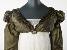 Spencer-With the rise of fashionable waistlines in women's dresses after around 1800, women's outerwear followed suit. This jacket with very short bodice and long sleeves was known as a spencer and was named after the male coat. It is made of a green silk, with brown satin puffs and silk cord decorating the deep V collar and the sleeves.  1817-1820