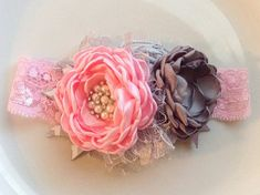Pink and gray fabric flowers. All handmade. Largest flower measures about 2.5 inches wide. On a lace elastic band. Can also be out on a