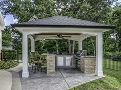 This impressive outdoor cooking area features a hip roof with arches over a decorative concrete patio. The ceiling is stained wood with a ceiling fan. The counters are granite with stone faced u-shaped area including bar seating. There is a True outdoor refrigerator, Napoleon grill and cabinets.