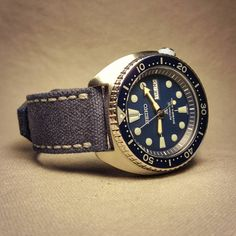 Seiko SRP773 on weathered blue canvas strap.