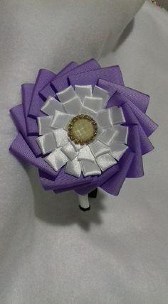 Tiara forrada com 2 Flores confeccionadas com fitas gorgurão nas cores Lilás e Branco. Com aplicação de Chaton. 1 em estoque.
