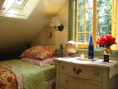 love the colorful patterned bedspread, the cute blue bottle and red flowers, and the adorable yellow windows
