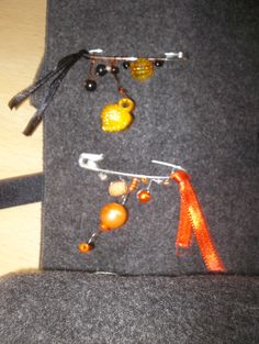 une épingle perles & ruban orange et une autre dans les tons de jaune & noir