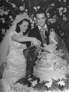 "Gloria Vanderbilt and Pasquale John 'Pat' DiCicco, cut their wedding cake on December 28, 1941. The cake was as dramatic as the bride's gown – particularly given that America had just joined WWII. The cake topper featured a bride dressed in a miniature gown that matched hers. Such a fashionable bride, it is little wonder her wedding dress has gone down as one of the greatest of the ""American royalty""."