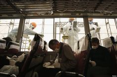 Workers carry out a radiation screening on a bus for a media tour at tsunami-crippled Fukushima Daiichi nuclear power plant of Tokyo Electric Power Co. in Fukushima prefecture, Japan, ahead of the second-year anniversary of the March 11, 2011 tsunami and earthquake.