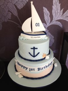 1st Birthday sail boat cake - Two tier sailboat ocean themed cake with a hand made fondant sail boat.  nb: customer came to me with a picture of similar cake to replicate so not an original design (not sure who's sorry)  Some changes were made though.
