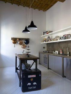 Paredes enlucidas. Suelo de madera pintado. Mobiliario metálico y elementos vintage, le dan el carácter industrial a esta cocina