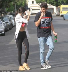 Laid-back: Kendall was joined by a male friend who matched her casual style in a graphic T-shirt, light wash skinny jeans, and high-top Converse sneakers
