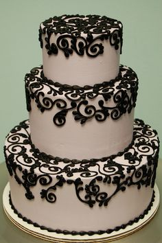 Gorgeous black scroll piping cake by Rise and Shine Bakery.