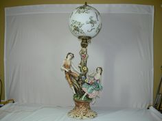 """Beautiful Vintage Large Capodimonte Figurine Table Lamp adorned with colorful ceramic flowers and two figurines perched on a tree branch. This large Capodimonte Table Lamp measures an impressive 41"""" in height and 17"""" in width. The beautiful china globe is hand-painted with burgundy, blue and orange flowers and green leaves and highlighted with gold swirls and measures 13"""" in diameter. The globe also has a """"Made In Italy"""" red label attached to it."""
