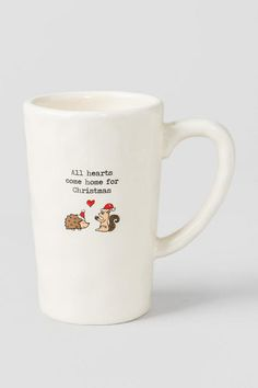 """""""All hearts come home for Christmas"""" - This cute holiday mug features a hedgehog & squirrel sharing love in Christmas hats! Give this mug to a special family member over the holidays!<br />%0D%0A<br />%0D%0A- 5"""" height<br />%0D%0A- Materials: ceramic<br />%0D%0A- Dishwasher & microwave safe<br />%0D%0A- By Natural Life"""