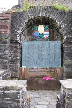 """The Roll of Honour of Clan MacRae in WWI, at Eilean Donan castle, featuring a quote from clan member John McCrae's """"In Flanders Fields"""". A wreath of poppies - also a symbol taken from the poem - rests below it."""