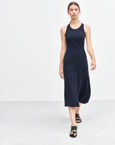 Body-con dress with scoop neck and stylish racer back. Easy and elegant, the dress is mid calf length, with a soft flare at the hem. Decorative seam detail in front.<br><br> •	Fitted bodice, flared at hem<br> •	Mid calf length<br> •	More sustainable ly