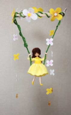 Children Mobile Girl in yellow dress on the swing. Made of