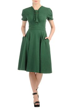 Front ties and puff sleeves define our retro-inspired dress modernized by a seamed bodice and stretchy cotton knit.